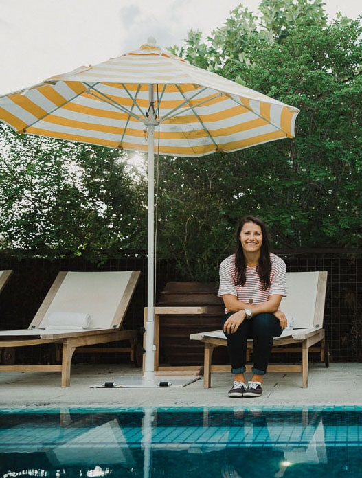 Female Nutrition Coach by a pool on a lounge chair under an umbrella