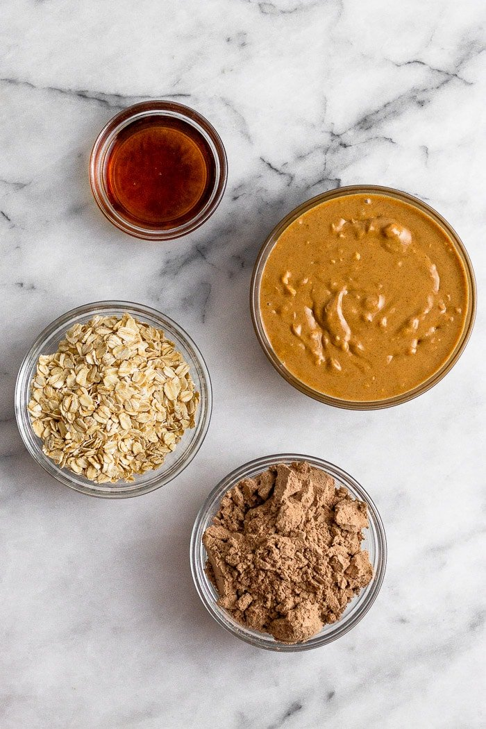 White countertop with a bowl of peanut butter, bowl of maple syrup, bowl of chocolate protein powder, and a bowl of oats.
