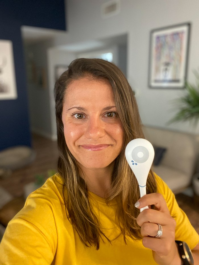 Girl in a yellow shirt with brown hair taking a selfie holding a Dasys Fertility Tracker.
