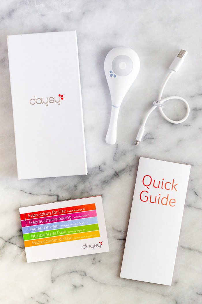 Daysy box, Daysy fertility monitor, charging cord, quick guide, and the Daysy manual on a white counter top.