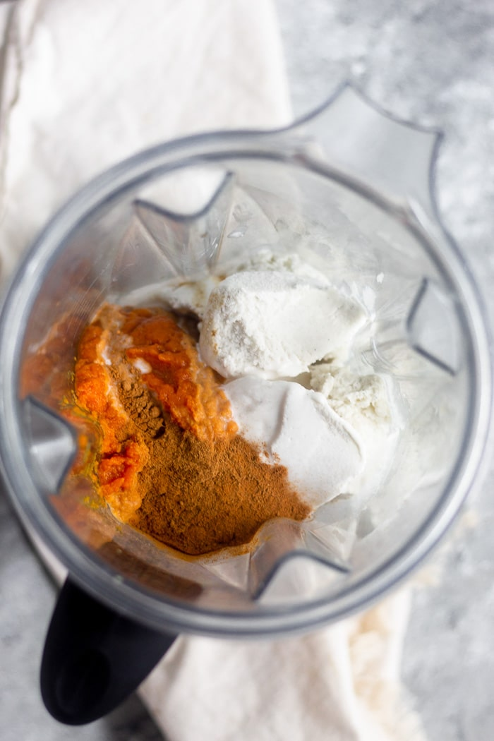 Overhead shot of a blender filled with vanilla ice cream, pumpkin puree, and spices.