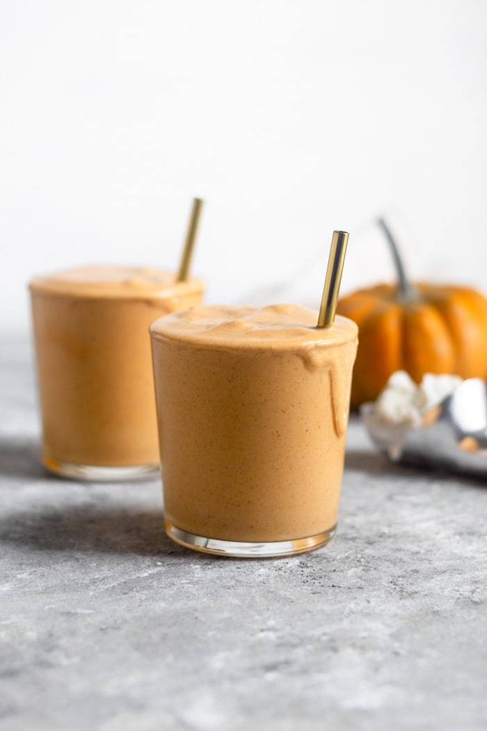 Two pumpkin vegan milkshakes in glass cups with straws in them. Behind them is an ice cream scoop with ice cream in it and a pumpkin.