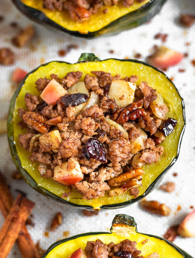 Sausage stuffed acorn squash filled with ground pork, apples, pecans, cranberries, and spices. It is sitting on a baking sheet surrounded by more stuffed squash with the filling scattered across on the silicone mat they are sitting on.