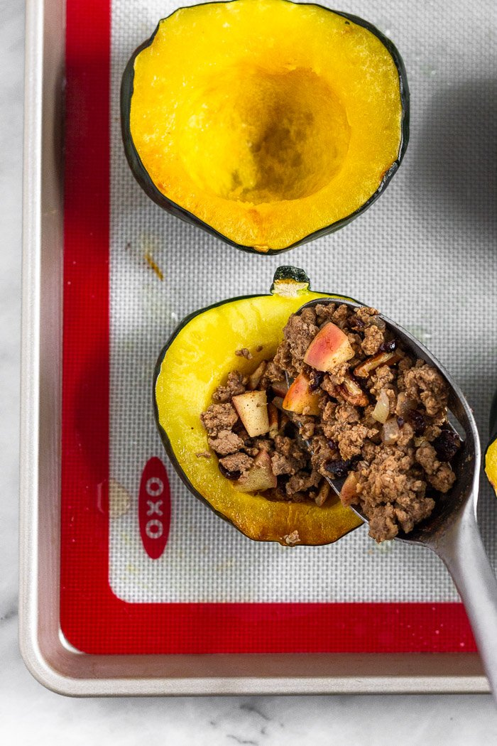 Roasted acorn squash on baking sheet that is being filled with a cooked sausage and apple mixture.