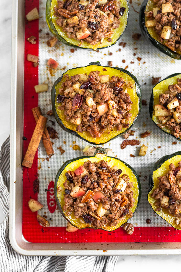 Sausage stuffed acorn squash on a baking sheet with a few pieces of the sausage and apple filling on the baking sheet as well. Two cinnamon sticks are also on the baking sheet.