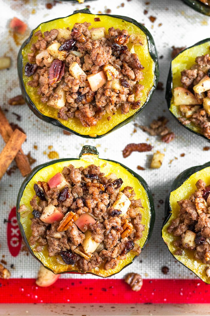 Overhead shot of stuffed acorn squash filled sausage and apples on a baking sheet. The filling is also scattered around the squashes.