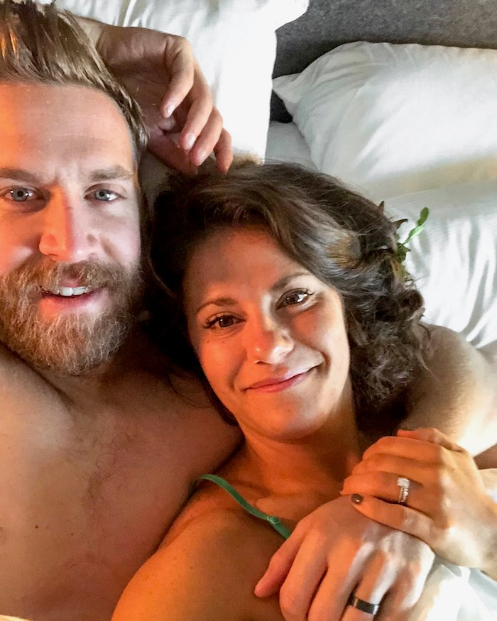 Husband and wife in bed the day after they got married. The wife is laying on husband's shoulder and they are both smiling.