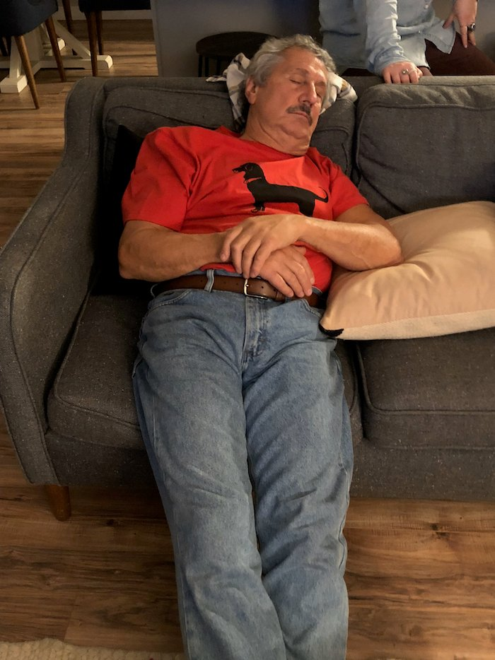 Old man passed out on a couch.