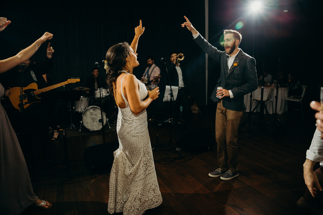 Both the bride and groom dancing on the dance floor and one hand up in the air and their finger pointed dancing and singing. A drink is in their other hand.