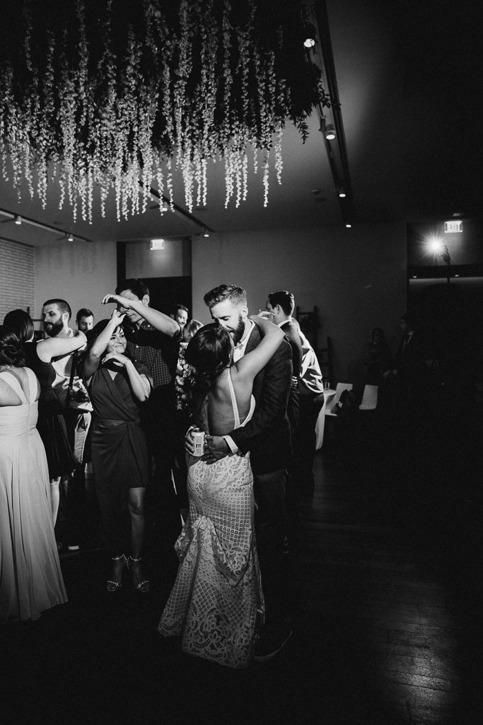 Bride and groom slow dancing on their wedding day with more people dancing behind them.