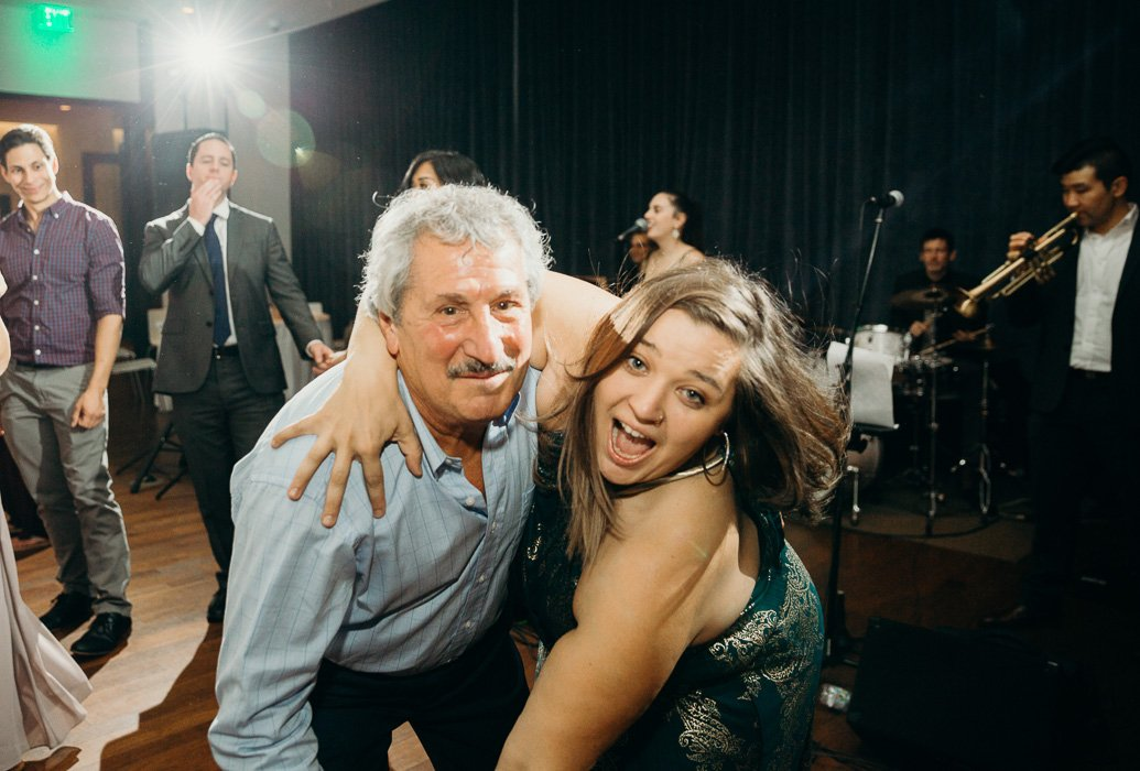 Older guy and a younger girl dancing at wedding.