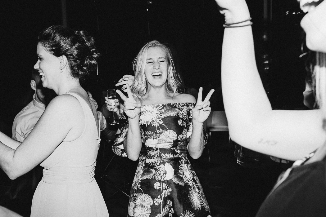 Girl holding up a double peace sign and laughing.