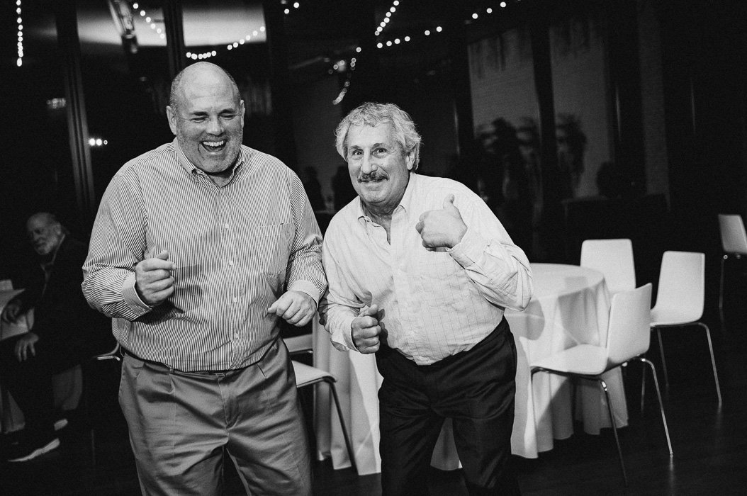 Two older guys dancing and laughing at a wedding.