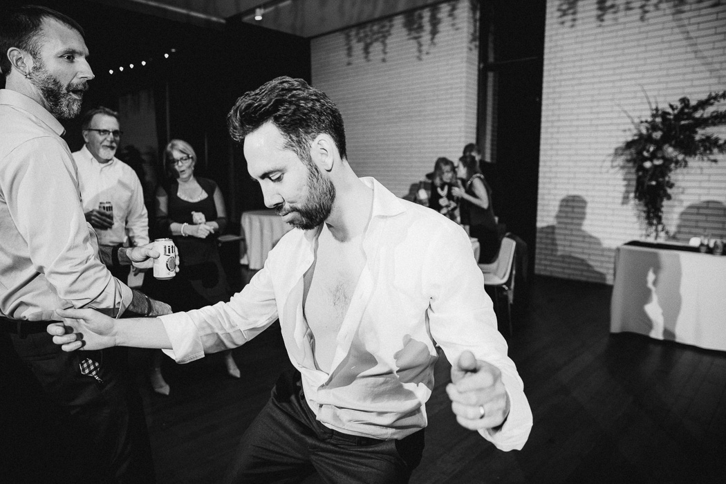 Guy with his shirt halfway unbuttoned dancing at a wedding.