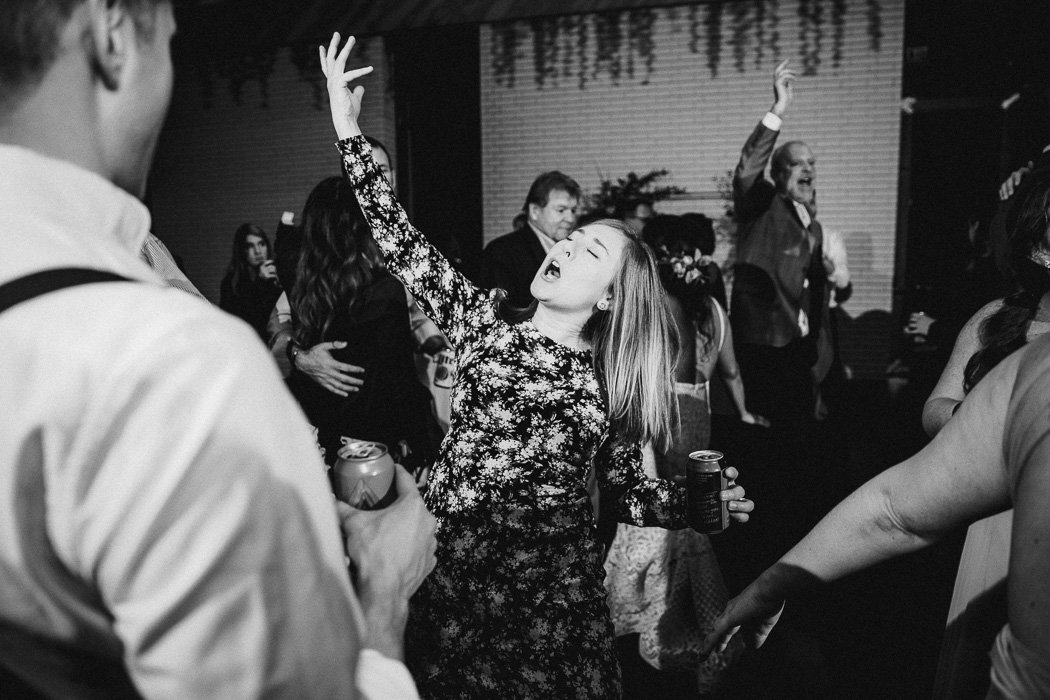 Girl with her hand in the air signing and dancing at a wedding.