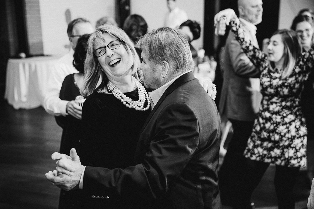 Older man and woman dancing with each other at a wedding.