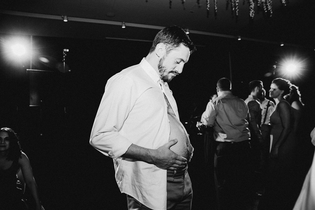 Guy with his shirt unbuttoned rubbing his belly at a wedding.