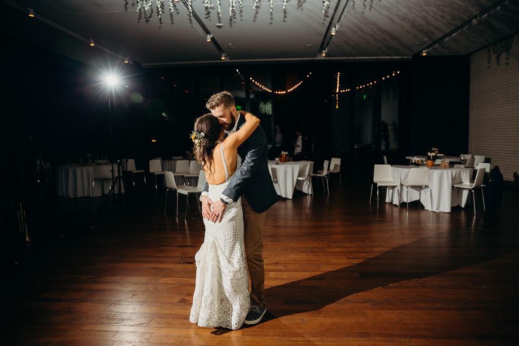 Bride and groom doing a last dance by themselves in an empty room. The groom's hands are on the bride's butt.