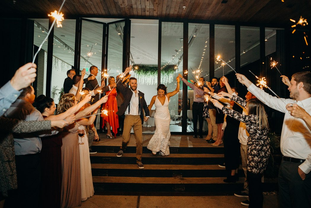 Bride and groom walking through a line of people on both sides with sparklers.