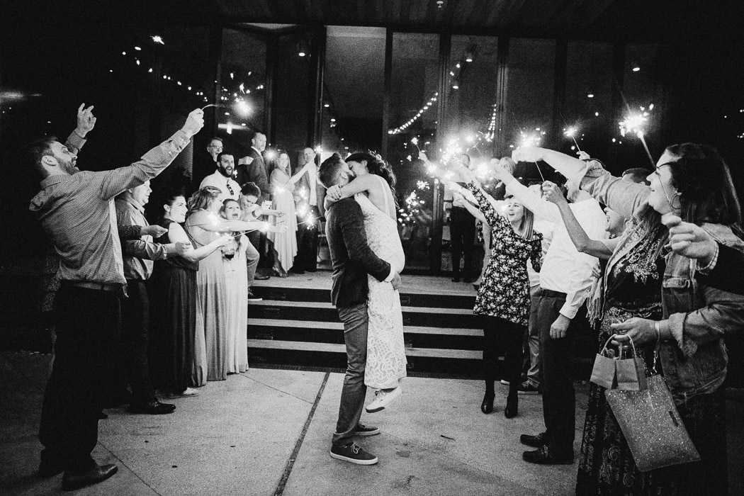 Bride and groom in the middle of two lines of people with sparklers. The groom is picking up the bride and they are kissing.