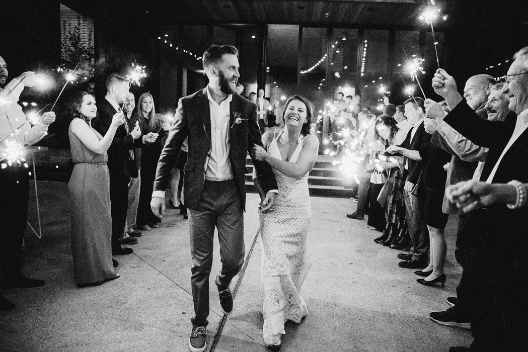 Bride and groom doing their exit of the ceremony through a line of sparklers. The bride has a huge smile on her face and the groom is looking over at the crowd.