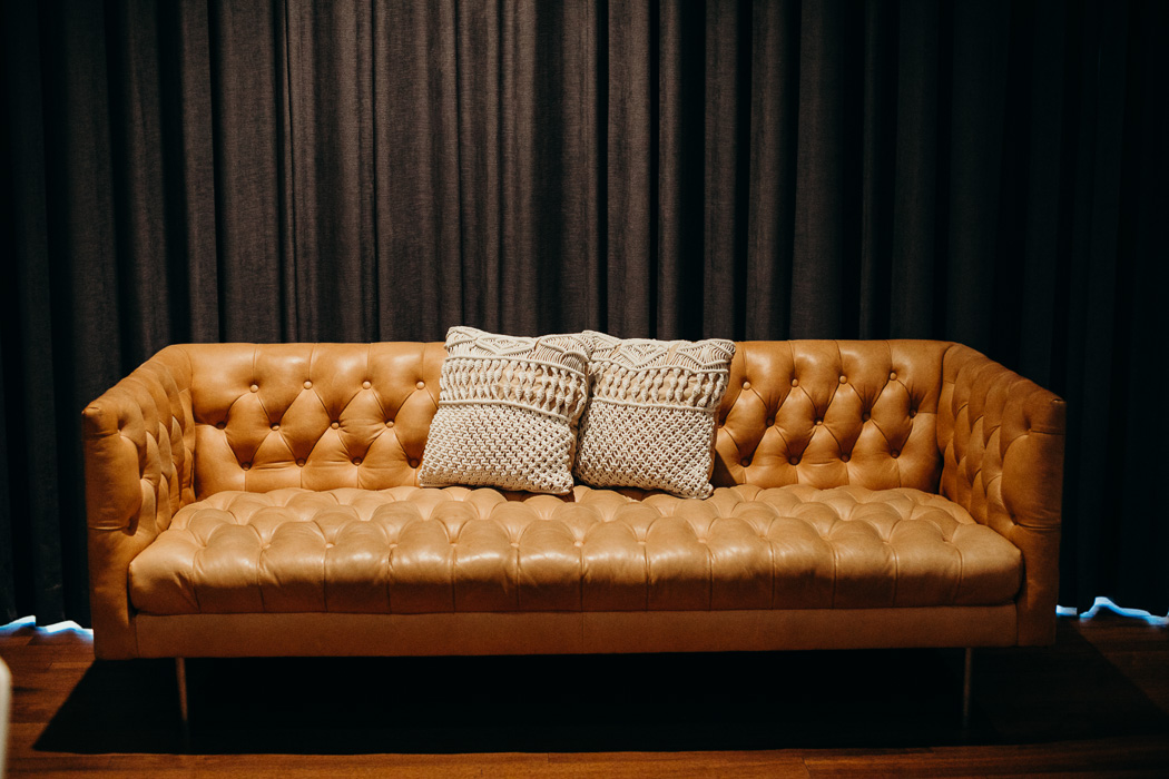 Brown leather couch with two pillows in front of a black curtain.