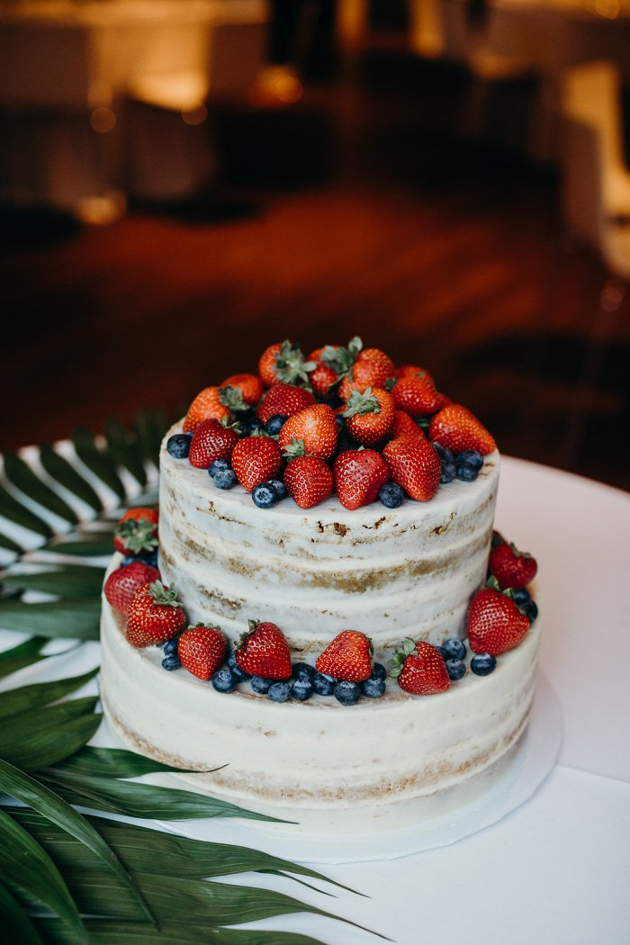 Two tier wedding cake with naked frosting and topped with strawberries and blueberries.