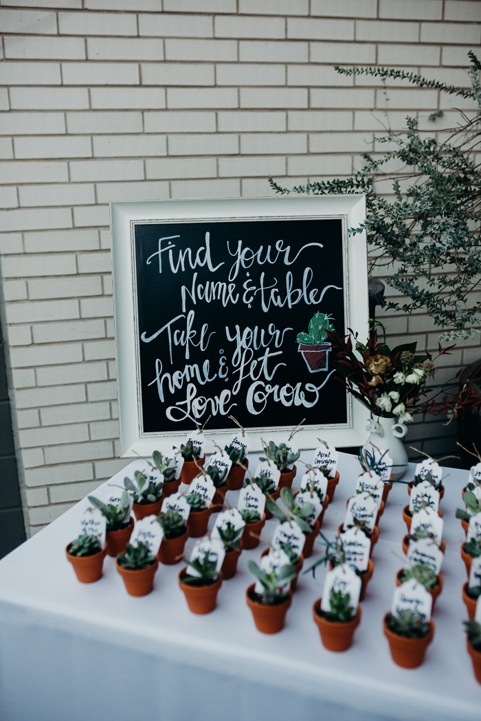"""Small succulents with people's names on a tag on them telling them where to sit for a wedding. Behind it is a sign that says """"find your name and table, take your plants home & let love grow."""""""
