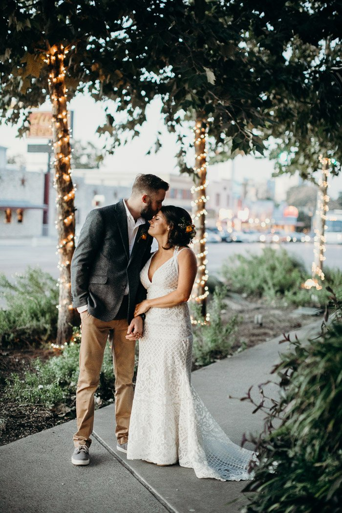Bridge and groom standing on a sidewalk with greenery and lights around them. The groom is kissing the bride on her forehead.