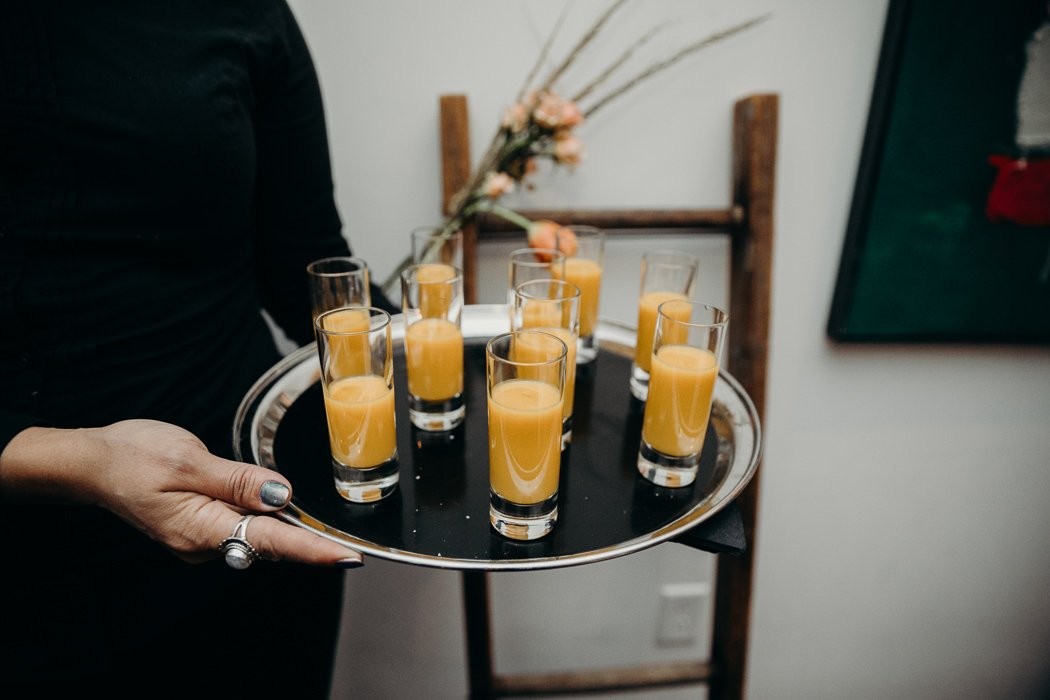 Serving platter with soup shooters on it.