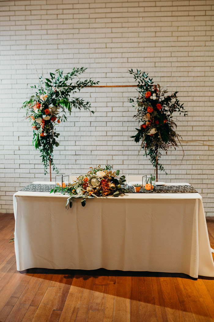 Bride and groom table at a wedding with the bouquet on it and an arch behind it with flowers. Behind it is a white brick wall.