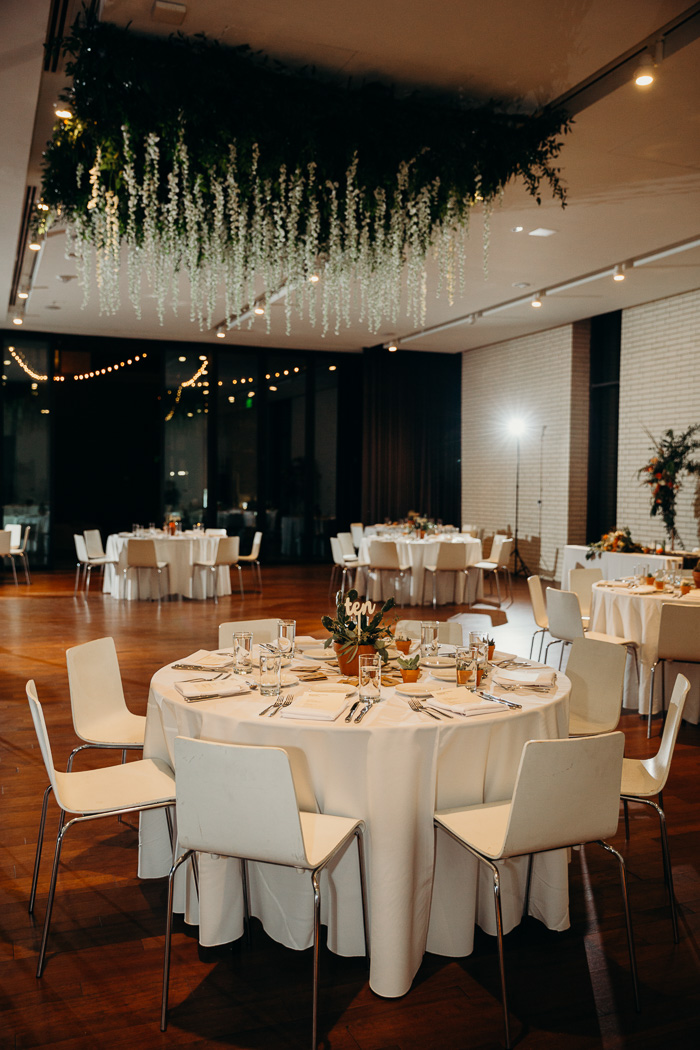 Tables and chairs set up for a wedding reception at South Congress Hotel. There is a large hanging from the ceiling with greens and flowers.