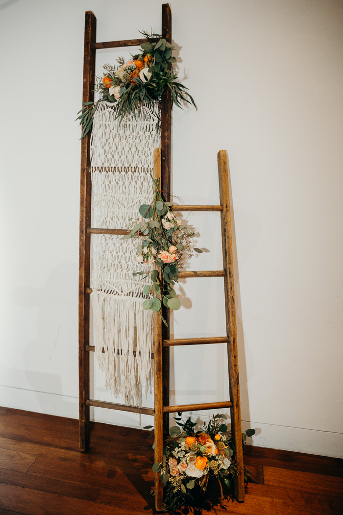 Two ladders decorated with flowers and a macrame hanging.