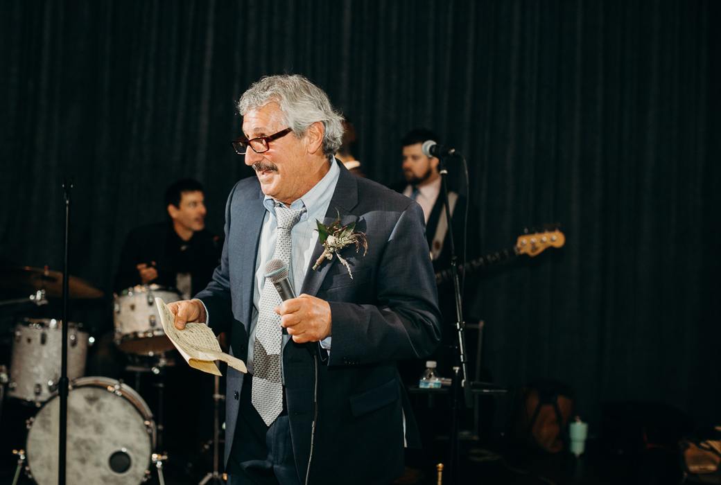 Father in a suit giving a speech at a wedding.
