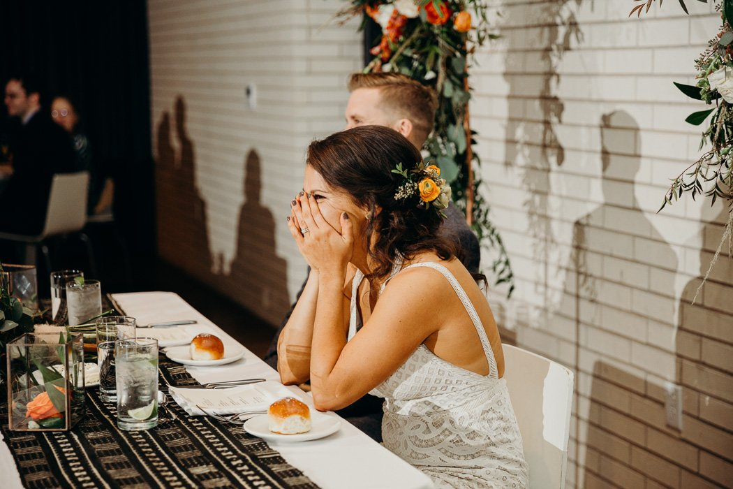 Bride and groom at the couple's table while someone is giving a speech. The bride's hands are over her mouth as she is laughing.