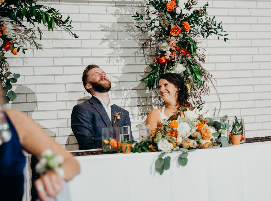 Bride and groom seating at their couples table on their wedding day. The groom has his head back laughing and the bride is looking at him smiling.