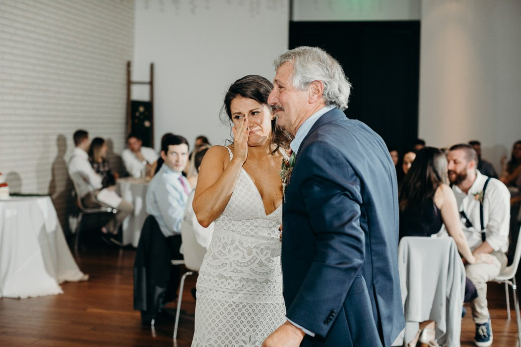 Bride wearing a boho wedding dress tearing up about to hug her dad.