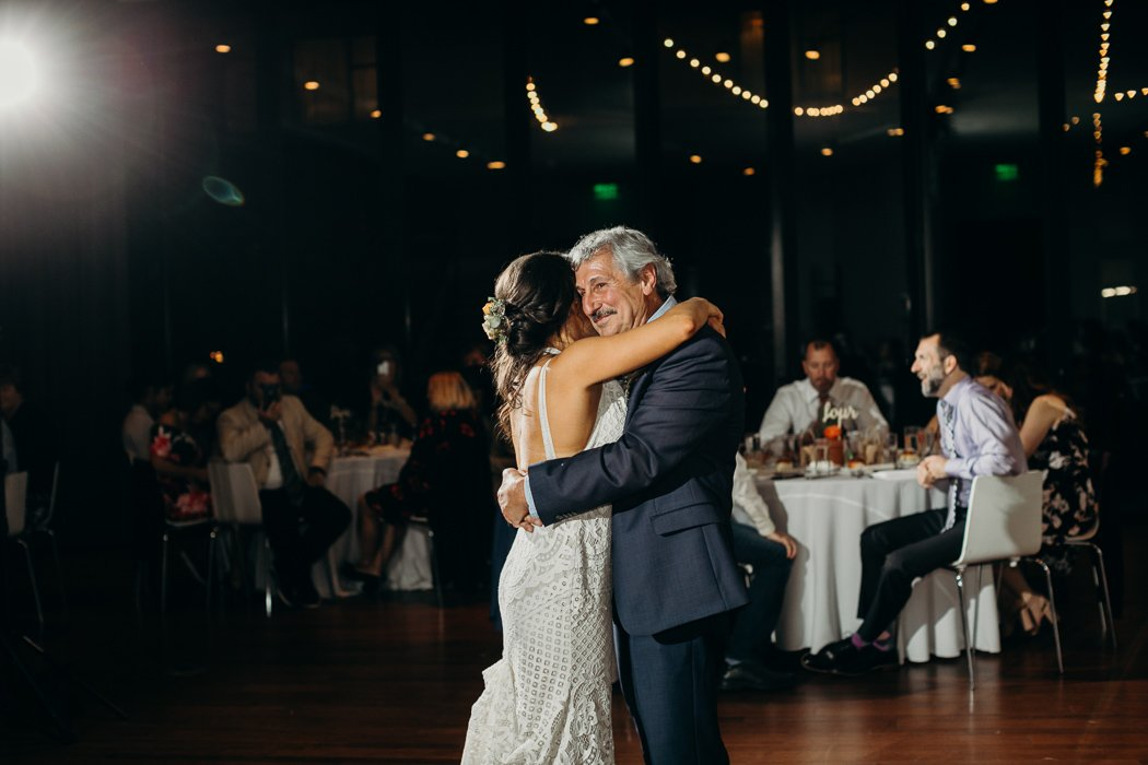 Father and daughter doing their dance at a wedding. They are happily embracing and smiling.