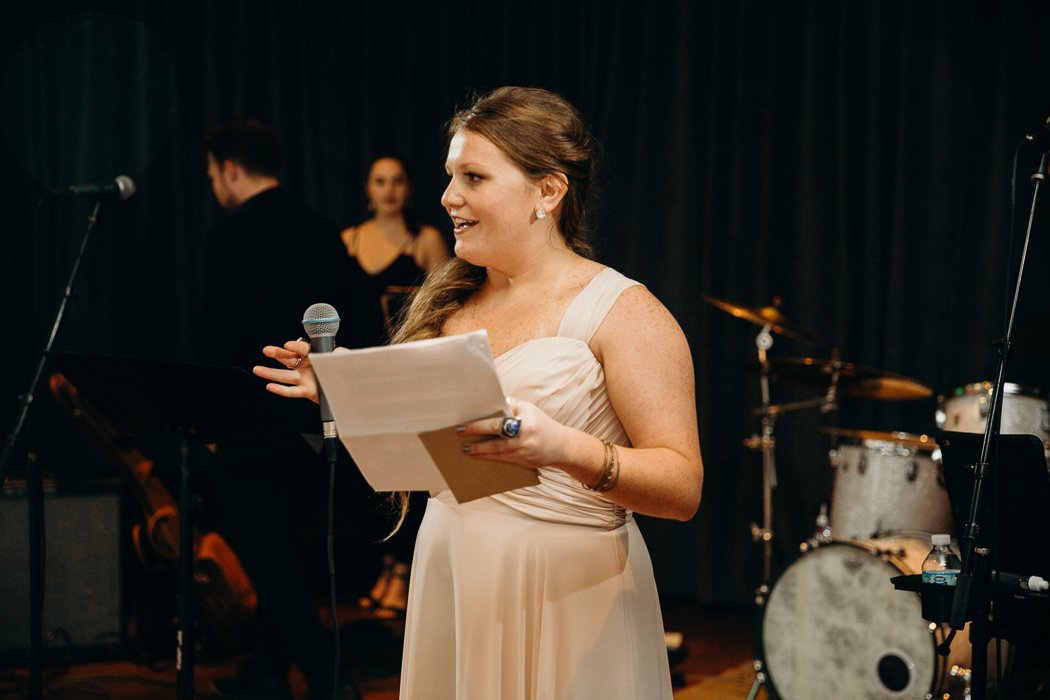 Maid of honor wearing a tan dressing giving a speech at a wedding.