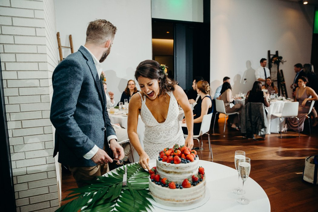 Bride and groom cutting their wedding cake. The groom is looking behind him and then bride is laughing. The cake is decorated with strawberries and blueberries.