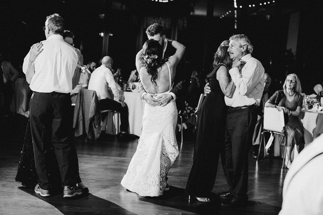 Bride and groom slow dancing with both of their parents slow dancing next to them.