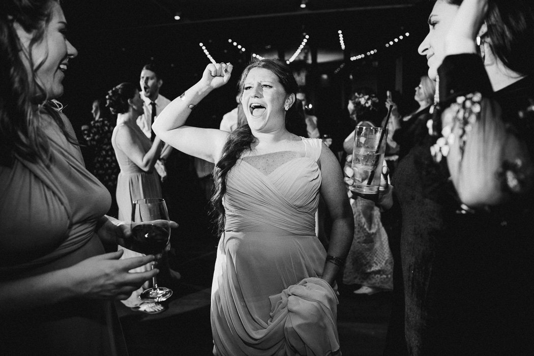 Girl with her fist in the air in the the middle of the dance floor singing.
