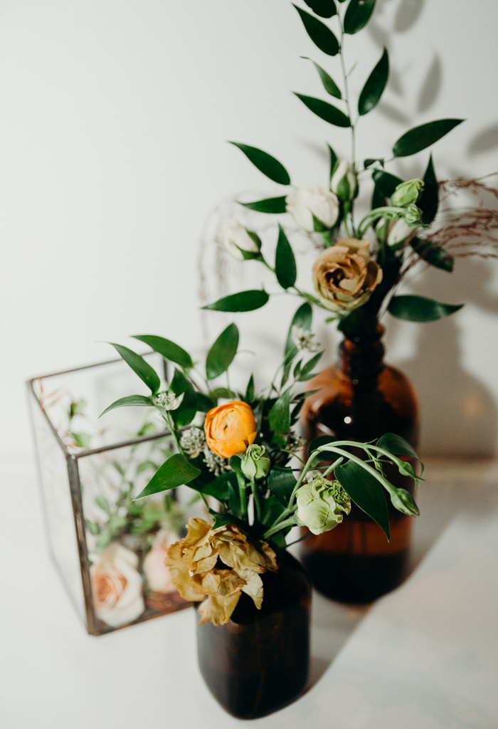 Rosebud vases filled with small flowers and greens.