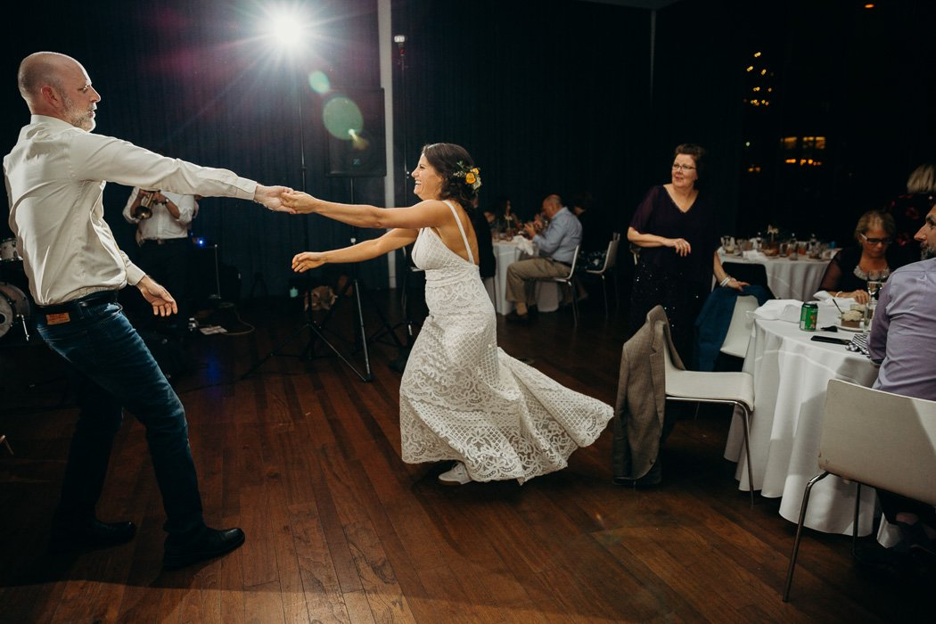 Bride dancing at her wedding with an older man. He is pulling her towards him and her dressing is flying back.