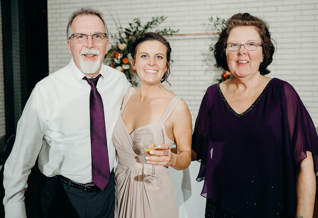 A dad, mom, and their daughter posing for a picture at a wedding.