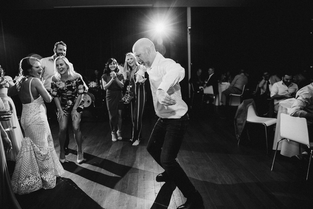 Man dancing in the middle of the dance floor at a wedding with people watching him.