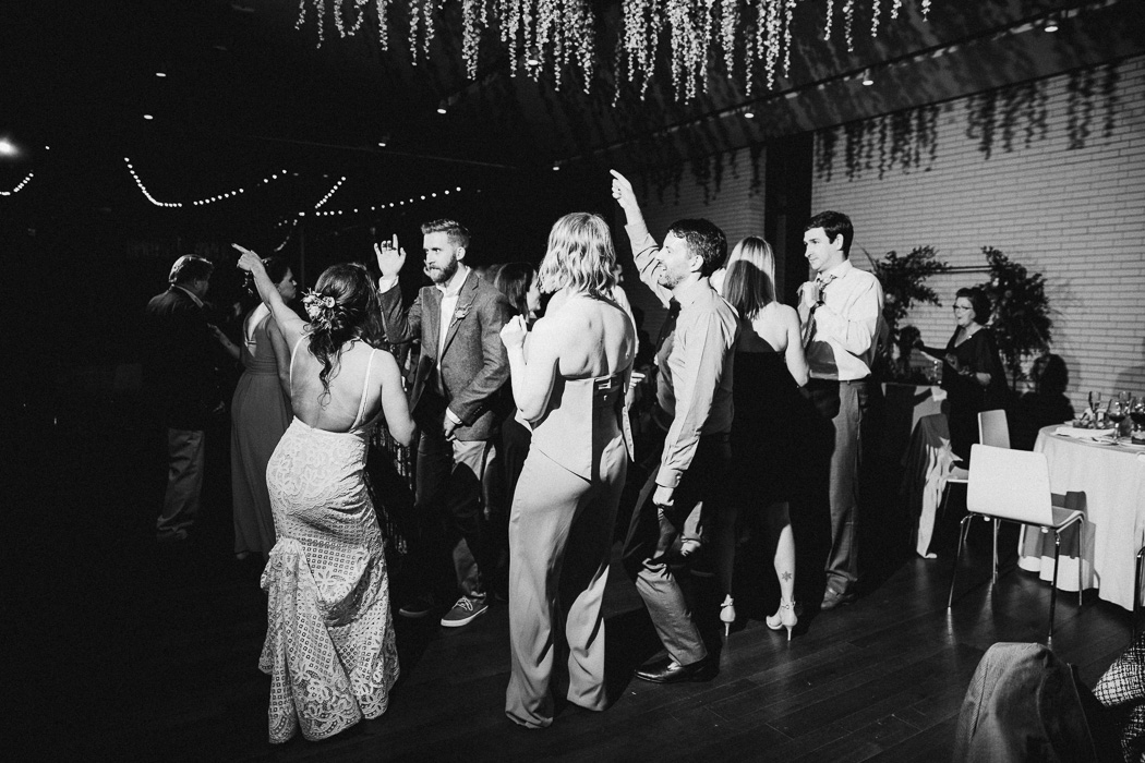 Group of people dancing at a wedding with the bride and groom.