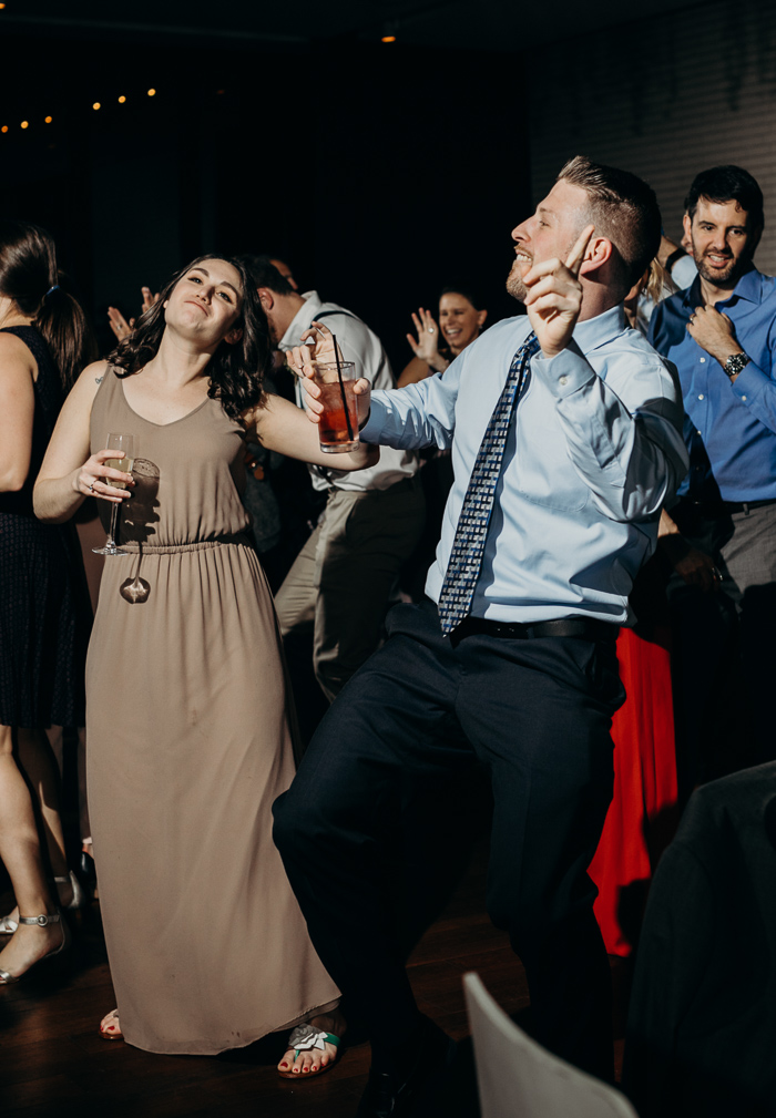 Guy and a girl with their one hand up and they other one holding a drink dancing at a wedding
