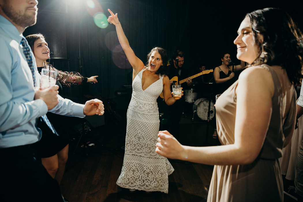 Bride dancing with a cup in one hand and her hand in the air in the other.