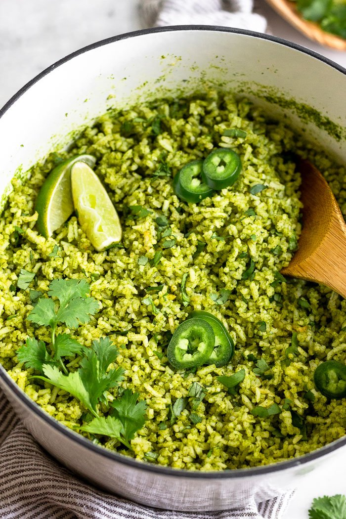 Close up of a large stock pot filled with arroz verde topped with jalapeños, limes, and cilantro. A wooden spoon is sticking out of it.